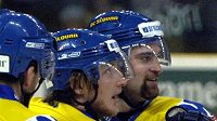 Hokejový obránce Jakub Grof (uprostřed) slaví se svými spoluhráči.