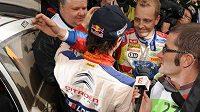 Mikko Hirvonen z týmu Ford (vzadu) gratuluje staronovému mistru světa v rallye Sébastianu Loebovi ze stáje Citroën.