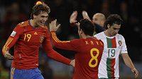 Španělští fotbalisté Fernando Llorente (vlevo) a Xavi se radují z branky.