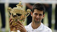 Srbský tenista Novak Djokovič s trofejí pro vítěze Wimbledonu.