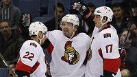 Hokejista Ottawy Senators Milan Michálek oslavuje gól se spoluhráči Filipem Kubou (vpravo) a Chrisem Kellym.