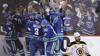 Hokejisté Vancouveru oslavují vítěznou trefu Raffiho Torrese v prvním finále Stanleyova poháru s Bostonem. Vpředu zklamaný kapitán Bruins Zdeno Chára.
