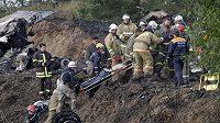 Záchranáři vyprošťují těla z havarovaného letadla