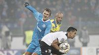Alexandr Bucharov z Petrohradu dotírá na brankáře APOELu Nikosia Paula Jorga v utkání Ligy mistrů.