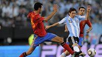 Lionel Messi (vpravo) prochází kolem Španěla Xaviho Hernandeze.