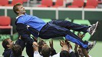 Kazašský tenista Andrej Golubjov nad hlavami svých spoluhráčů po vyřazení českého týmu.