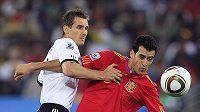 Miroslav Klose z Německa (vlevo) bojuje o míč se Sergio Busquetsem ze Španělska v semifinále MS v JAR.