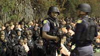 Policisté hlídají naštvané demonstranty.