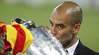 Trenér Barcelony Pep Guardiola s trofejí pro vítěze Ligy mistrů.