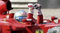 Vítězné gesto Fernanda Alonsa ve voze Ferrari po letošním triumfu v Monze.