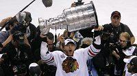 Marián Hossa v hloučku novinářů se Stanley Cupem nad hlavou