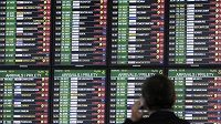 Muž sleduje tabuli se zrušenými spoji na letišti v Praze