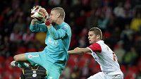 Brankář Lille Ludovic Butelle sbírá ze vzduchu míč před dotírajícím Volešákem ze Slavie.