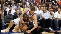 V nebasketové pozici zápolí o míč Spencer Hawes z Filadelfie (v bílém) s Dwyanem Wadem z Miami Heats.