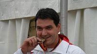 """Jiří Lipták """"ochutnává"""" bronzovou medaili, kterou vystřílel v trapu na MS v Mnichově."""