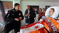 Slávisté Martin Vaniak (vlevo) a Martin Latka sledují utkání s těžce nemocným fanouškem Slavie Boleslavem Pánkem, který si přál vidět utkání svého klubu přímo na stadiónu.