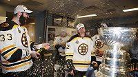 Zdeno Chára (vlevo) stříká šampaňské na spoluhráče z Bostonu po vítězství ve Stanleyově poháru. Bouřlivý mejdan právě začal...