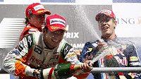 Giancarlo Fisichella (vlevo), Kimi Räikkönen a Sebastian Vettel (vpravo) se radují na stupních vítězů po GP Belgie