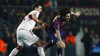 Hvězda Barcelony Lionel Messi (vpravo) se snaží proklouznout okolo Zdravka Kuzmanoviče ze Stuttgartu.