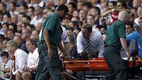 Pořadatelé odnášejí Bacaryho Sagnu ze hřiště během utkání Arsenalu s Tottenhamem.