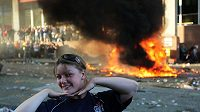 Fanynka Vancouveru pózuje fotografovi zatímco se za ní odehrávají nepokoje
