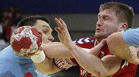 Slovinec Zvizej a český házenkář Sklenák bojují o míč během utkání na ME v Rakousku.