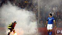 Italský fotbalista Gianluca Zambrotta (vpravo) se dívá na světlici, kterou likviduje hasič.