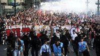 Za asistence policejních těžkooděnců pochodují po Čechově mostě fanoušci pražské Slavie, kteří vyrazili na Letnou na tradiční derby Sparta - Slavia.