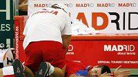 Zraněný srbský tenista Novak Djokovič v péči fyzioterapeuta.
