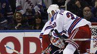 Václav Prospal z NY Rangers padá při derby s Islanders na brankáře Dwayna Rolosona.