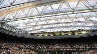 Britský tenista Andy Murray servíruje pod zataženou střehou centrálního kurtu ve Wimbledonu proti Stanislasu Wawrinkovi ze Švýcarska.