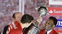 Kapitán Internacionalu Bolivar přebírá pohár od legendárního Pelého.