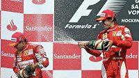 Těžko říct, jak Fernando Alonsovi (vpravo) a Felipe Massovi chutnal na stupních vítězů pěnivý sekt, když o výsledku závodu rozhodl místo nich někdo v pozadí.