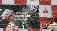 Pilot McLarenu Jenson Button (vlevo) se spolu se svým týmovým kolegou Lewisem Hamiltonem raduje z triumfu v GP Číny.