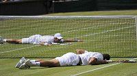 Tenisté Novak Djokovič (za sítí) a Jo-Wilfried Tsonga po výjimečné výměně v semifinále Wimbledonu.