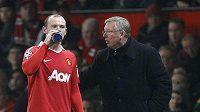 Kouč Manchesteru United Alex Ferguson (vpravo) udílí pokyny útočníkovi Wayneovi Rooneymu.
