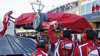 Mechanici Ferrari vykládají v boxech monopost Felipeho Massy.