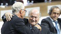 Spokojený úsměv na tváři staronového prezidneta FIFA Seppa Blattera (vlevo), v roli gratulanta německá fotbalová legenda Franz Beckenbauer. V pozadí šéf UEFA Michel Platini.