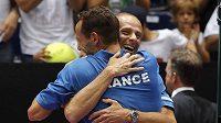 Tenista Michael Llodra oslavuje s nehrajícím kapitánem francouzského daviscupového týmu Guy Forgetem postup do semifinále Davis Cupu.