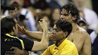 Od tenisty Rafaela Nadala (vpravo) odvádí bezpečnostní služba fanouška (vlevo), jenž Nadala objal a políbil.