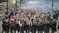 Polští fotbaloví fanoušci s policejní asistencí pochodují přes Čechův most na Letnou.