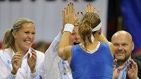 Lucie Šafářová se raduje z vítězství nad Anou Ivanovičovou, vlevo je spoluhráčka Lucie Hradecká.