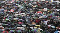 Lidé se shovávají před deštěm pod deštníky.