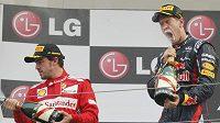 Sebastian Vettel si vychutnává vítězství, vlevo Fernando Alonso.