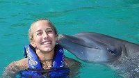 Také ve vodě je Sarah Reinertsenová jako doma... Plavání s delfíny dostala jako odměnu za zdolání Ironmana.