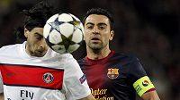 Záložník Paris Saint-Germain Javier Pastore hlavičkuje míč před Xavim z Barcelony (vpravo).