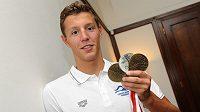 Plavec Jan Micka ukazuje tři medaile z juniorské ME v plavání během tiskové konference dne 15. července 2013 v Praze.