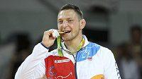 Olympijský vítěz Lukáš Krpálek zakousnutý do zlaté medaile.