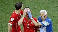 Švýcarský obránce Steve von Bergen (uprostřed) je ošetřován lékařem. Vlevo je další obránce Stephan Lichtsteiner.