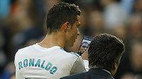 Zraněný Cristiano Ronaldo z Realu se prohlíží v mobilu při odchodu ze hřiště při utkání s La Coruňou.